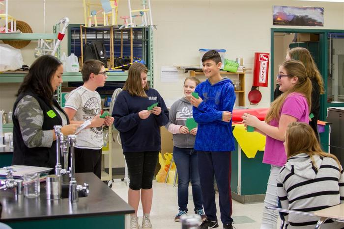 Shantelle Davidson (far left) guides eighth graders through an activity where a student volunteer has to make ends meet with only a minimum wage job after dropping out of school.