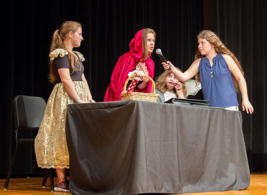 Calista Conder (6th Gr., far right) plays a journalist interviewing Little Red Riding Hood played Savannah Doughty (6th Gr., middle) with Grandmother Hood played by Caitlin Nelson (8th Gr., left) looking on.