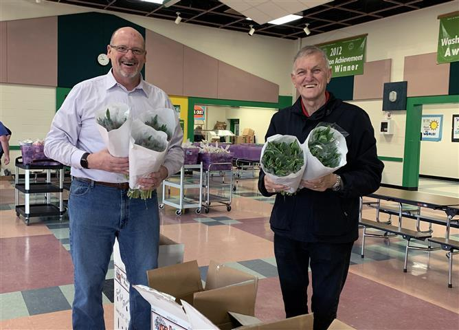 Benno Dobbe (right) gives 550 tulip bunches to Woodland Public Schools staff