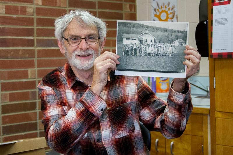 When John Huffman and his wife first arrived to teach in 1978, they were pleased to discover that the original schoolhouse in the photo Huffamn is holding here had been replaced with a newer facility.