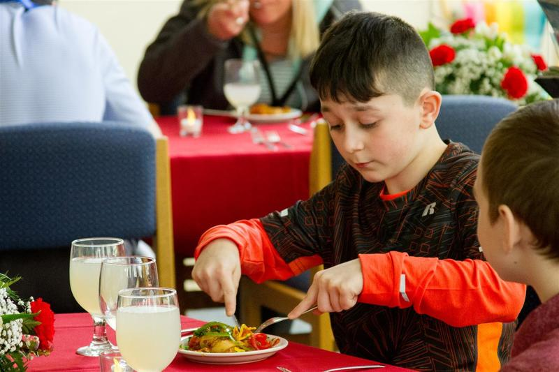 During a class lesson before the event, students learned how to use an entire set of silverware in preparation for enjoying a meal with multiple courses.